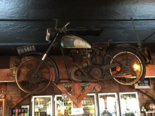 Old things nailed to the bar wall, including a motorbike.